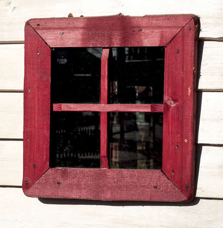 Red window of a old wooden house photo