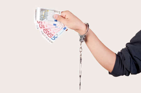 hand with handcuffs holding money photo