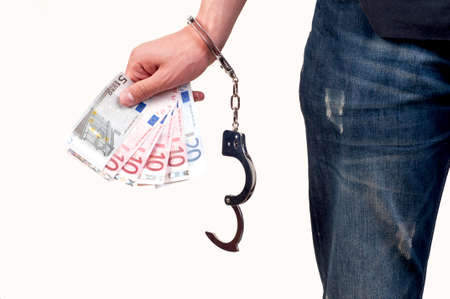 Hand with handcuffs holding money on white background photo