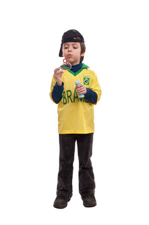 little boy blowing soap bubbles on white background