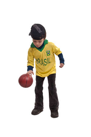little boy playing with a small basketball ball on a white background Stock Photo