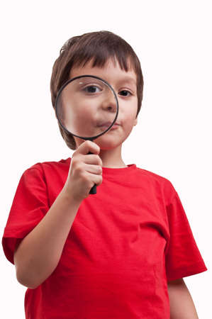 little boy playing with magnifier on white background