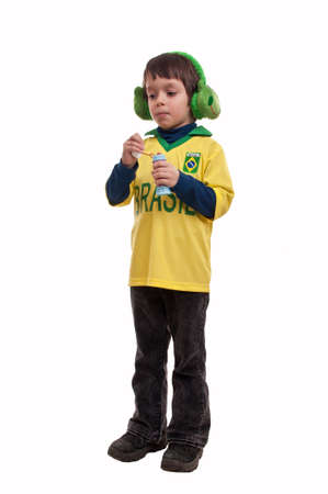 little boy wearing a pair of fluffy ear muffs in shape of frog playing with soap bubbles photo