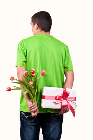 gift behind back: Man hiding flowers and gift box behind his back Stock Photo