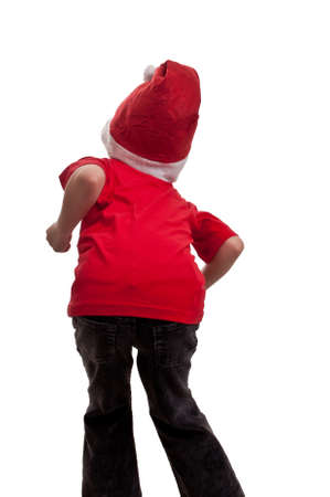 Back of a happy little boy in hat of Santa Claus enjoying that Christmas is coming on white background