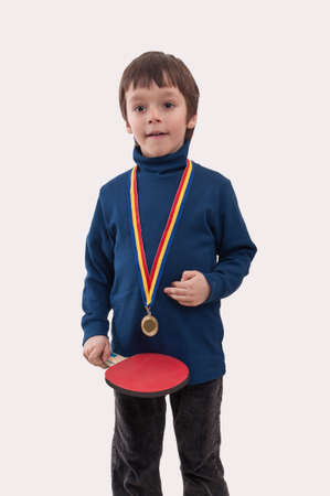 little boy with gold medal at his neck and table tennis racket in hand photo