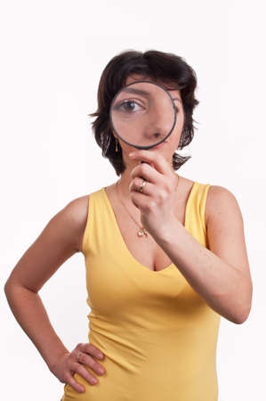Young woman with magnifying glass at her eye