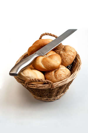 Bread loave in a wicker basket with knife on top photo