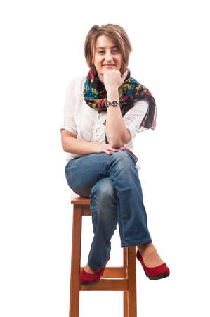 Beautiful smiling young woman sitting on a chair Stock Photo