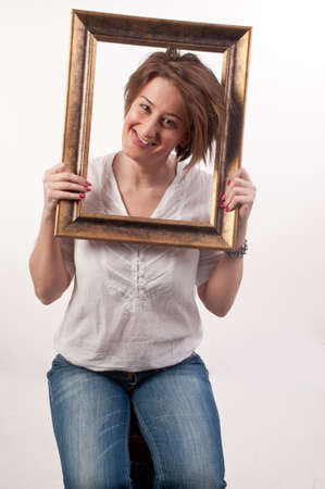 Funny beautiful woman holding around her face a frame photo
