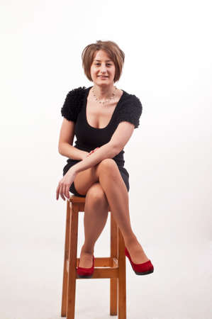 young elegant woman in black dress sitting on chair Stock Photo