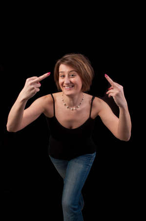 revenge: Attractive young woman making obscene hand gesture showing middle fingers over black background