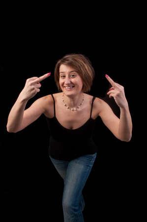 venganza: Mujer joven y atractiva que hace gesto obsceno con la mano mostrando el dedo medio sobre fondo negro