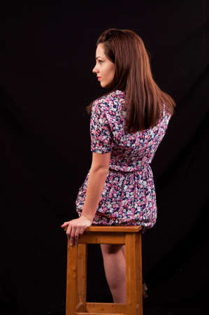 Beautiful brunette sitting on a chair and looking over her shoulder against a black background photo
