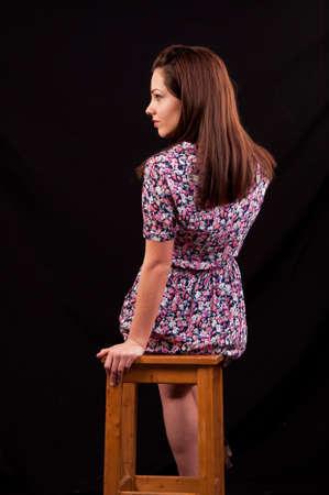 mujeres sentadas: Hermosa morena sentada en una silla y mirando sobre su hombro contra un fondo negro