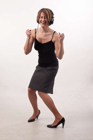 Funny photo of young casual business woman listening to music on headphones, singing and dancing