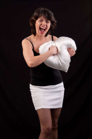 Angry woman strikes with fury a heart-shaped pillow on black background