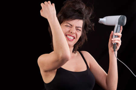 attractive cheerful woman blows dry her hair with hairdryer, over black photo