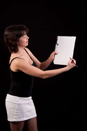 Studio shot of young woman writing notes on clipboard and showing them photo