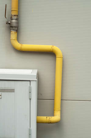 heat register: yelow pipes and gas meter on gray wall Stock Photo
