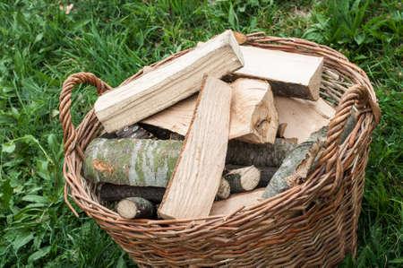 Closeup basket of cut logs fire wood on green grass, environmental concept