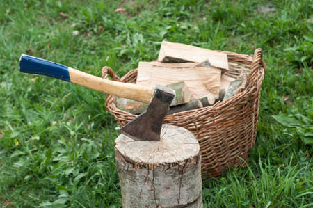 An axe stuck in a log in front of basket with logs fire photo