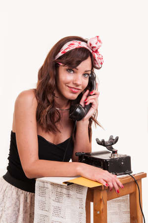 Beautiful and fashion young woman with a retro look posing with a vintage phone