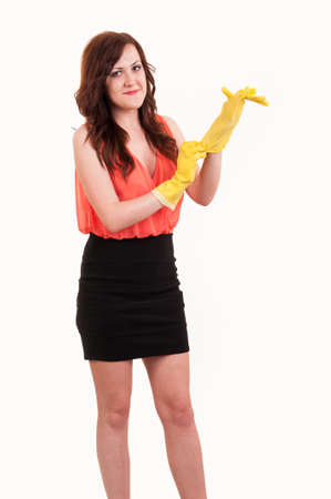 houseclean: funny picture of young business woman puting on hands yellow rubber glove over white background Stock Photo