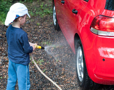 Little boy playing with water hose, wash car