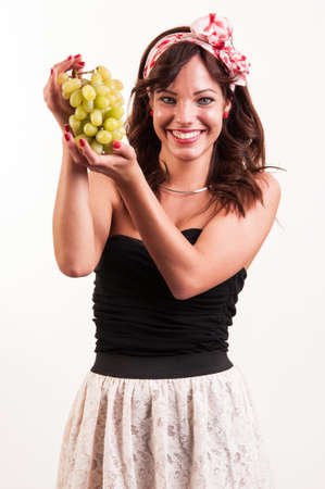 studio shot, portrait of attractive young caucasian woman showing green grapes isolated on white
