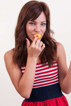 Close up young woman eating citrus fruit
