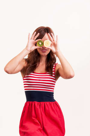 Healthy fruit funny woman holding kiwi and lemon fruit for her eyes photo