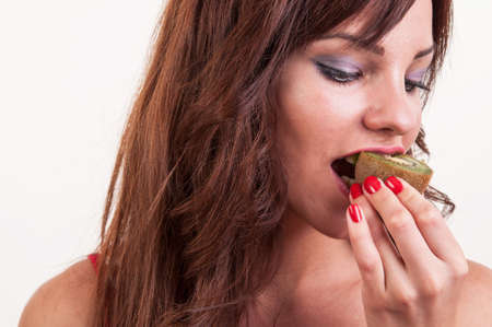 portrait of young beautiful woman eating a piece of kiwi