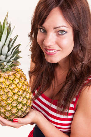 Portrait of young beautiful woman showing pineapple Stock Photo