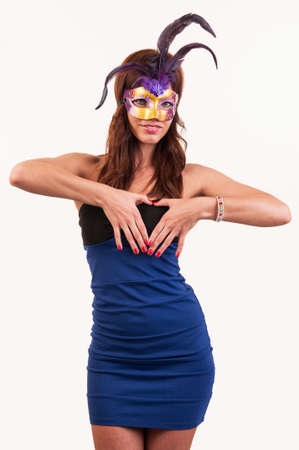 beautiful young woman in a purple carnival mask, forming heart with hands Stock Photo