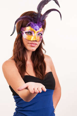 Beautiful young woman with a mask showing with hand - place for your product