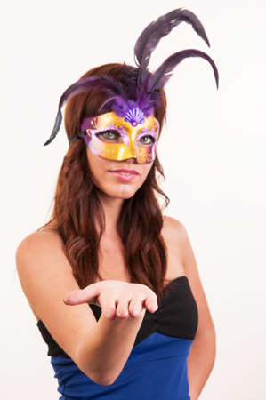 Beautiful young woman with a mask showing with hand - place for your product photo
