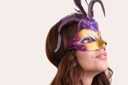 Portrait of a beautiful young woman in a purple carnival mask, copy space photo