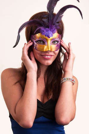 Beautiful young woman hides her beauty under purple mysterious venetian mask