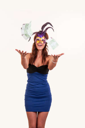 Happy young woman in purple mysterious venetian mask throw money. Masquerade
