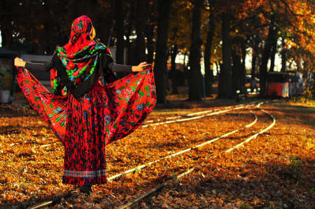 Romantic young gypsy woman pulls up dress and walks on the railroad trying to keep balance