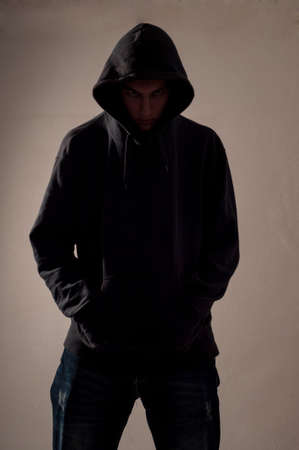 teenager with hoodie look ahead against a dirty gray wall