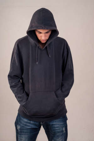 hooded: teenager with hoodie looking down against a dirty gray wall Stock Photo