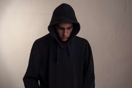 teenager with hoodie looking down against a dirty gray wall Stock Photo