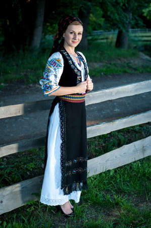 Full length of young beautiful woman posing outside in Romanian traditional costume Stock Photo - 20896744