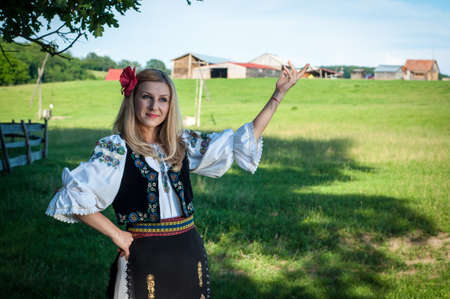 beautiful woman with red flower in her hair posing in Romanian traditional costume Stock Photo - 20896758