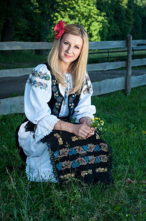beautiful singer with flowers posing in traditional costume, romanian folklore Stock Photo - 20896759