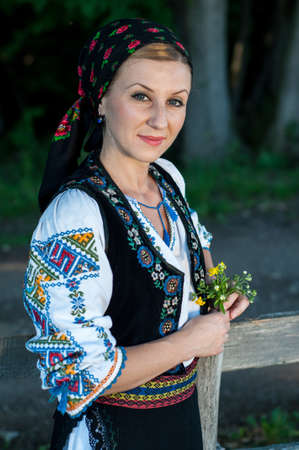 ethnology: beautiful singer with flowers in her hands posing at countryside, romanian folklore