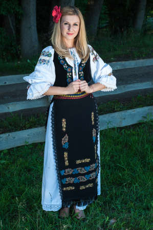 Full length of young beautiful woman with red flower in her hair posing in Romanian traditional costume