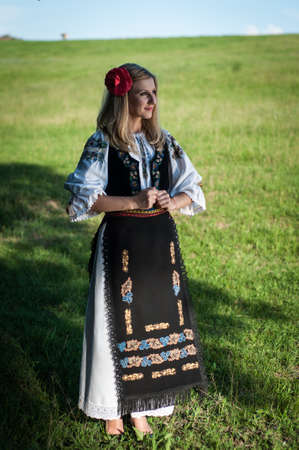 Full length of young beautiful woman with red flower in her hair posing in Romanian traditional costume Stock Photo - 20896789